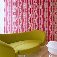 A curved green sofa with pull-out ottoman stands in front of a wall covered in pink and white wallpaper - all designed by Karim Rashid