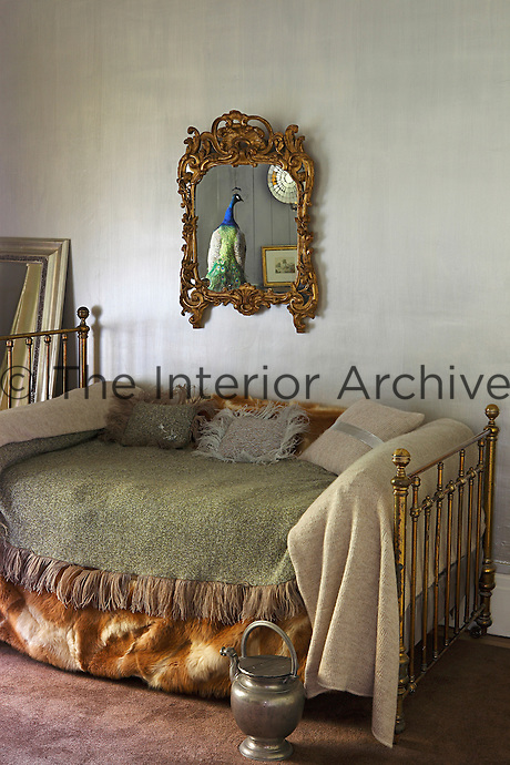 "In the ""Peau d'ane"" bedroom the large brass bed has been dressed as a daybed creating an air of opulent decadence"