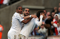Saturday, 20 October 2012<br /> Pictured: Michu of Swansea (R) celebrating with fellow players Ashley Williams (L) and Chico Flores (C).<br /> Re: Barclays Premier League, Swansea City FC v Wigan Athletic at the Liberty Stadium, south Wales.