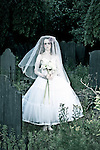 Female youth with sad expression holding flowers wearing white wedding dress standing in graveyard