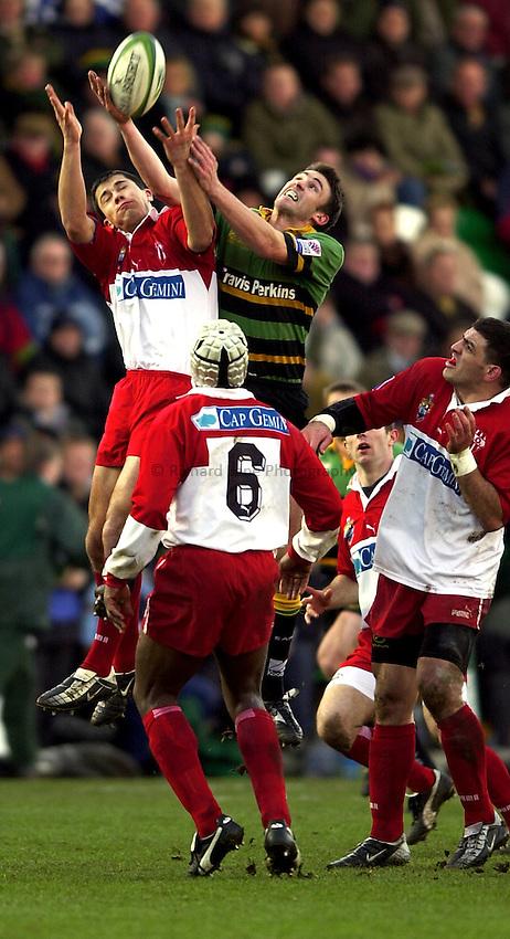 Photo. Richard Lane. .Northampton Saints v Biarritz. Heineken Cup. 11/01/2003..John Leslie and Jean-Emmanuel Cassin get up for a high ball.