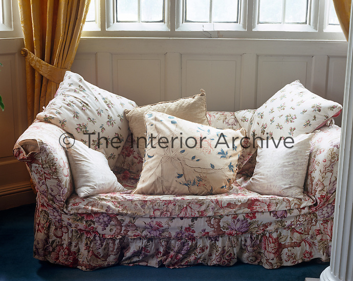 A cosy sofa is upholstered in a chintz fabric with floral-patterned cushions piled on top
