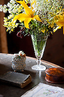 A posy of fresh flowers stands alongside a number of antique keepsakes on a table in a bedroom