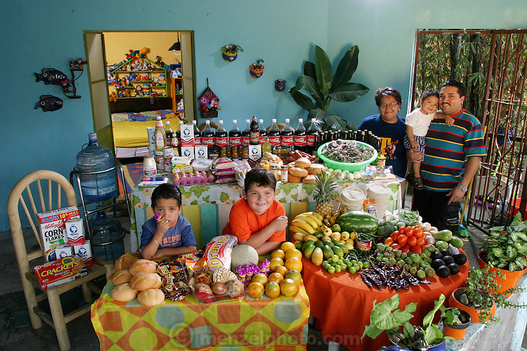 (MODEL RELEASED IMAGE). The Casales family in the open-air living room of their home in Cuernavaca, Mexico, with a week's worth of food. Marco Antonio, 29, and Alma Casales Gutierrez, 30, stand with baby Arath, 1, between them. At the table are their older children, Emmanuel, 7, and Bryan, 5. Cooking method: gas stove. Food preservation: refrigerator-freezer. Favorite foods? Marco Antonio: pizza. Alma: crab. Emmanuel: pasta. Bryan: crab and candy. Arath: chicken. /// The Casales family is one of the thirty families featured in the book Hungry Planet: What the World Eats (p. 218). Food expenditure for one week: $189.09 USD. (Please refer to Hungry Planet book p. 219 for the family's detailed food list.)
