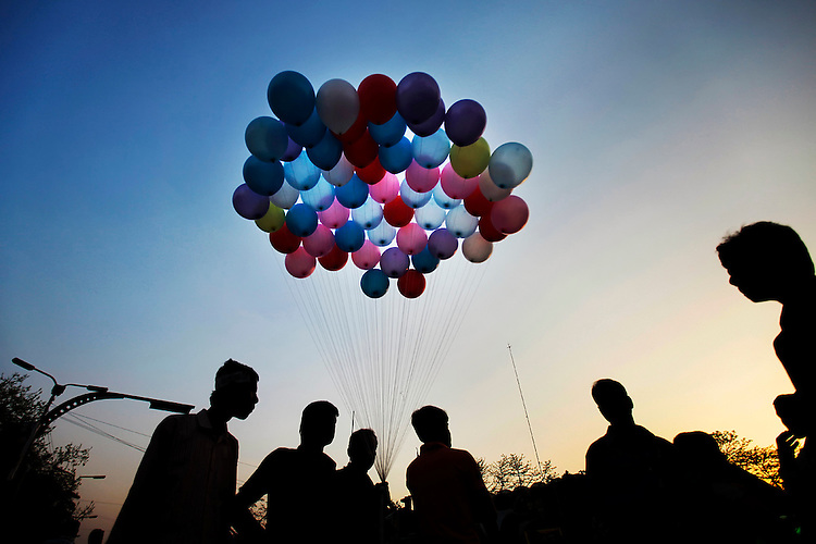 A street vendor stands with balloons on a road in Dhaka, Bagladesh.