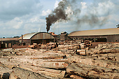 Juruena, Mato Grosso, Brazil. Industrial-sized sawmill timber yard full of tree trunks with black smoke coming out of a chimney.