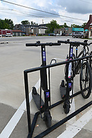 NWA Democrat-Gazette/SPENCER TIREY Goat Scooters, scooters that are rented by scanning a QR code, are seen on a bike rack outside Heros Coffee and Roastery shop on 8th and A street, Wednesday July 10, 2019 in Bentonville.