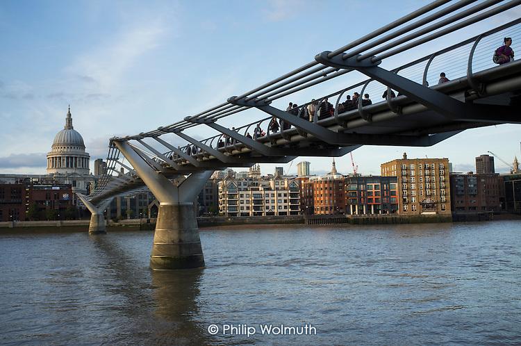 Pedestrians cross the Millenium Bridge across the River Thames, London.