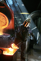 Chad Ettenhofer works to remove impurities from the 10,000 pounds of melting scrap iron at D & L Foundry in Moses Lake, Washington on August 16, 2006. The factory produces iron manhole covers. His gloves and protective suit are designed to insulate his hands, lower arms and body from temperature extremes and hot splashes fro molten metals or other hot liquids. His Class B hard hat and face shield protect him from flying or falling objects, and from electrical hazards with high-voltage shock and burn protection up to 20,000 volts.