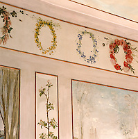 In a bedroom of the atelier of 19th century painter Charles Daubigny a series of delicately painted floral wreaths adorns the trompe l'oeil frieze above the painted panels