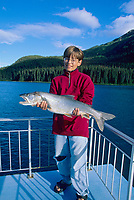 Boy holds his Lake trout catch, Atlin Lake, Atlin, BC Canada