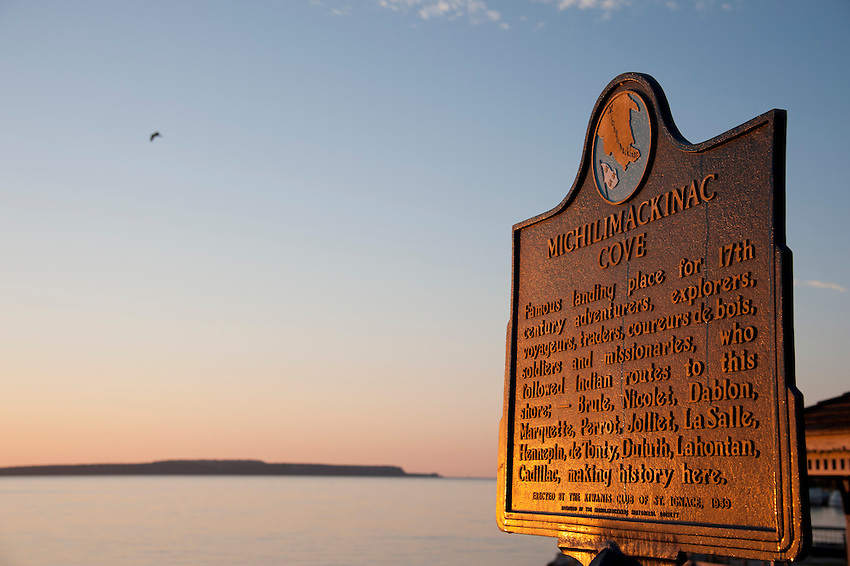 Mackinac Island historical marker and Lake Huron at St. Ignace Michigan at dawn.