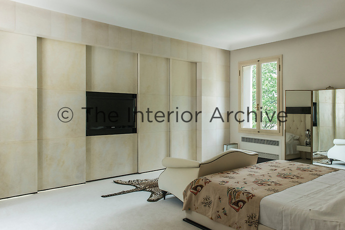 The master bedroom is decorated in neutral tones with floor to ceiling storage. A built-in sliding panel conceals a flat-screen television opposite the double bed.