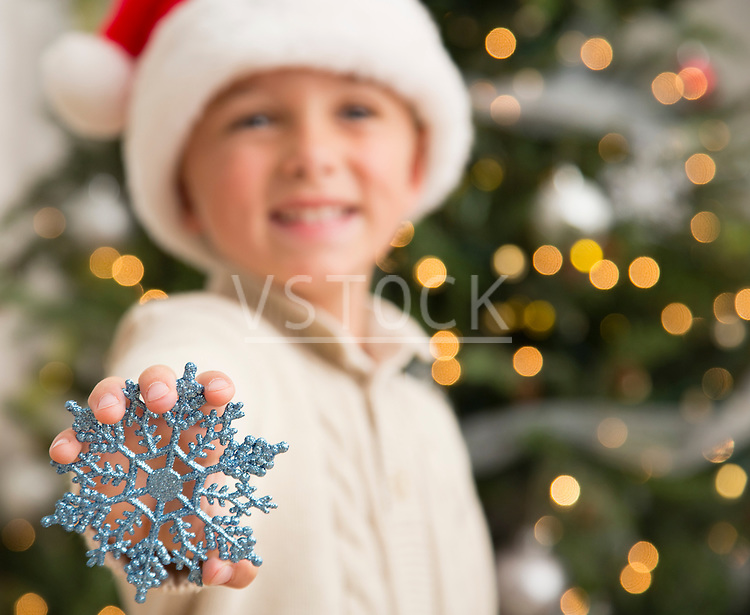 Boy (6-7) holding decorative snowflake