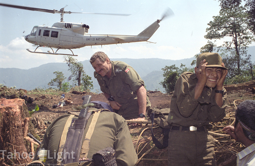 Guatemalan URNG rebel troops and united nations peace keepers cover themselves during the landing of a UN helicopter that has come to pick up an arms cache that the rebels turned in as part of the peace accords.
