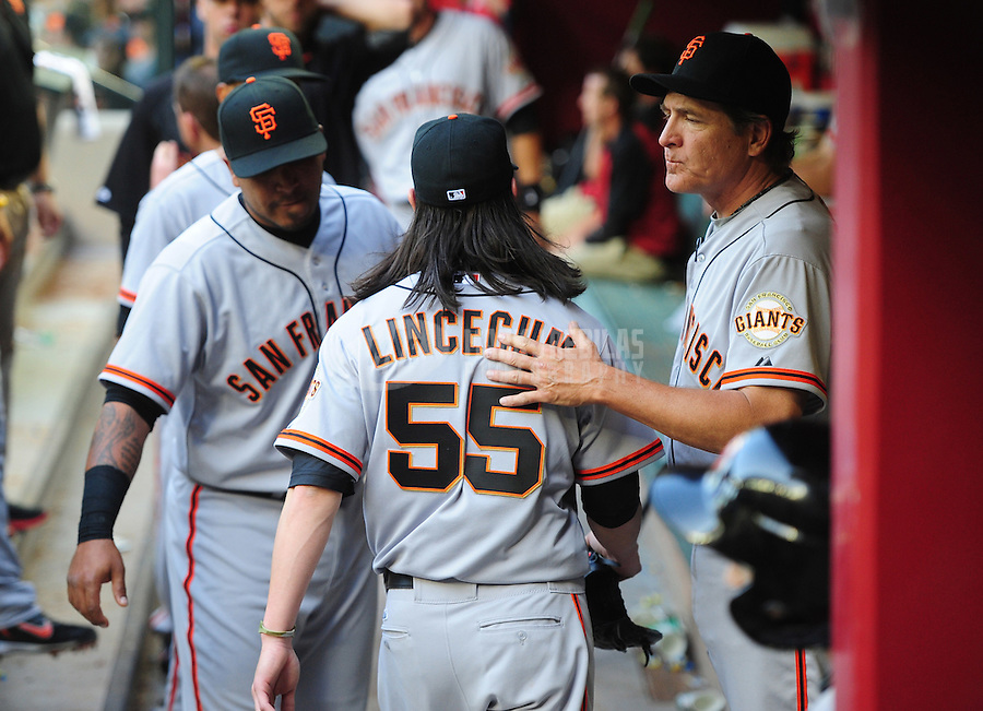 Apr. 6, 2012; Phoenix, AZ, USA; San Francisco Giants pitcher Tim Lincecum (55) is embraced by pitching coach Dave Righetti after being pulled from the game in the sixth inning against the Arizona Diamondbacks during opening day at Chase Field.  Mandatory Credit: Mark J. Rebilas-