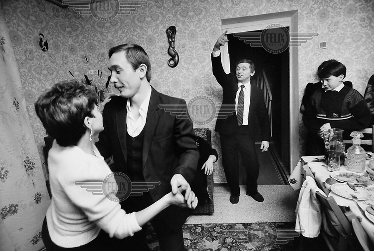 A couple dance at a New Year's party in a miner's apartment.