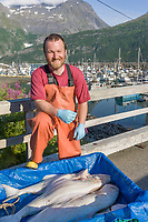 Local halibut fisherman John Guffey poses with a catch in Whittier, Alaska.