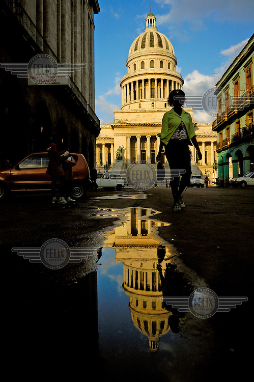 A reflection of the National Capitol Building (El Capitolio) is captured in a pothole puddle...