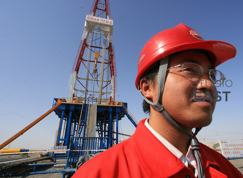 An ingeneer stands by a derrick in Petrochina's Tazhong oil factory, in Tarim Oilfield, Xinjiang province, China, on October 11, 2006. Photo by Servais Mont/Pictobank