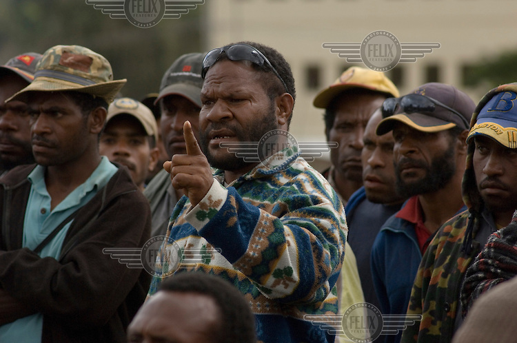 A crowd of men from Tari gather in Mendi for the counting of ballot boxes from three electorates in the Hela region following a ballot dispute during the 2007 general elections. The men travelled for four hours to protest against the transferral of around 200 ballot boxes from Tari to Mendi. The boxes had been held back in Tari for two weeks until a judicial ruling forced the handover and the ballots were moved for counting to Mendi via helicopter and under armed security. Since the dispute appeared to be linked to employment issues rather than voting security, the Electoral Commission later negotiated a compromise whereby more Tari residents would be included in the official Mendi counting process and paid as counting officials.