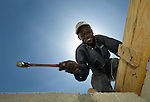 The sun behind him, a man hammers nails at a school under construction in Tabarre Issa, Haiti. The construction is supported by the United Methodist Committee on Relief (UMCOR), as part of its assistance to Haitians affected by the 2010 earthquake.