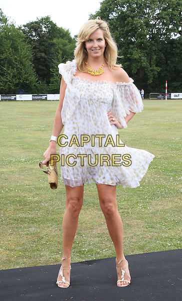 PENNY LANCASTER STEWART .Duke Of Essex Polo Trophy at Gaynes Park, Epping, Essex, England, UK,.July 4th 2009..full length white sheer puff sleeve off the shoulder dress blouson hand on hip strappy sandals gold straw clutch bag print.CAP/ROS.©Steve Ross/Capital Pictures