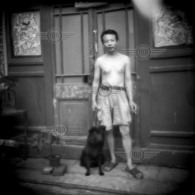 A local resident smoking a cigarette is pictured with his dog in a hutong neighbourhood. The traditional hutong housing areas are being systematically demolished to make way for new modern developments in the city.