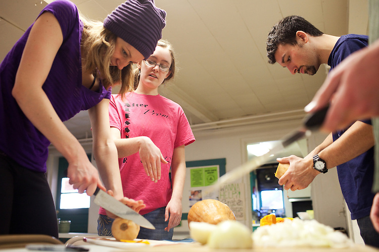 Student volunteers Madeline Gall (left) and Jack Obora (right) get direction from Judy Pratt-Harrington (middle) at the United Campus Ministry building during their weekly Saturday free meal in Athens, Ohio on January 19, 2013. Photo by Chris Franz