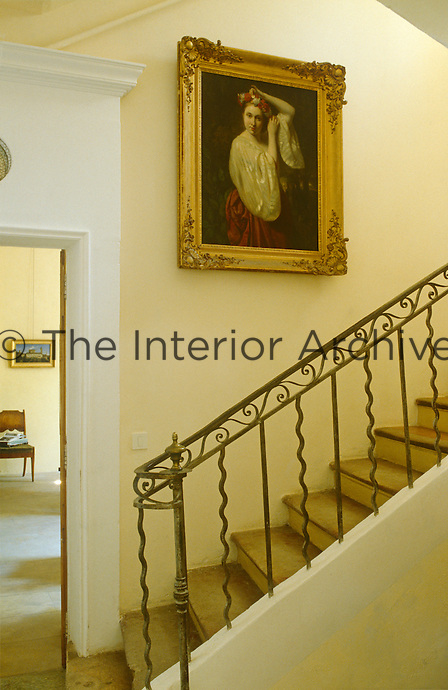 A gilt-framed portrait hangs above a stone staircase with a contemporary wrought-iron balustrade