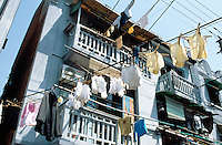 "China. Shanghai. Downtown. City center. Laundry-lined in the old ""French Concession"" area. Early morning,  some underwears, many white gloves and a shirt just washed are now drying outside the balconies of an old traditionnal house. © 2002 Didier Ruef"