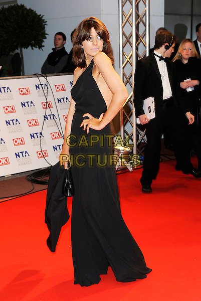 CLAUDIA WINKLEMAN .At the National Television Awards, held at O2 Arena, London, England, UK, January 20th 2010..arrivals TV NTA NTAs full length black dress long maxi hand on hip side .CAP/FIN.©Steve Finn/Capital Pictures.