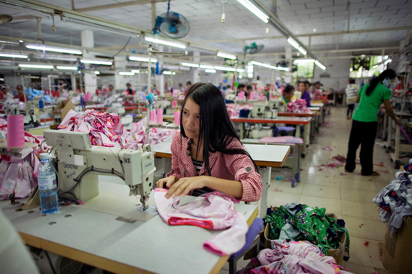 A garment factory worker stitches clothing at an un-named, un-marked factory in Phnom Penh, Cambodia, September 15, 2010.