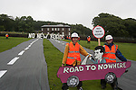 20 activists dressed in roadbuilders' high viz clothing and hard hats roll out a fake road in the field  immediately below Crag Hall, Cheshire in who's  grounds  the Chancellor  of the  exchequer George Osbornes has a residence .  <br /> The protest was made to highlight the expected  release of money for roadbuilding schemes throughout  the UK in the imminent spending  reivew on Wednesday 26th June