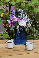 Coffee pot filled with flowers on a table in Taos, New Mexico