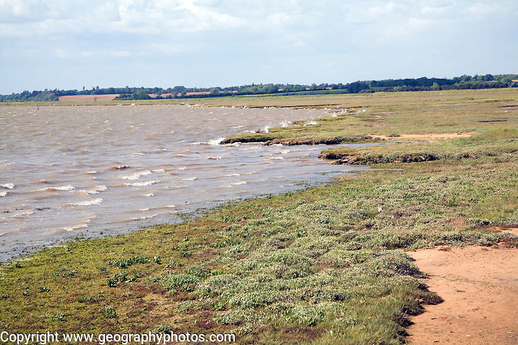 Strong winds create waves causing erosion to saltings River Deben from Bawdsey looking upstream, Suffolk, England