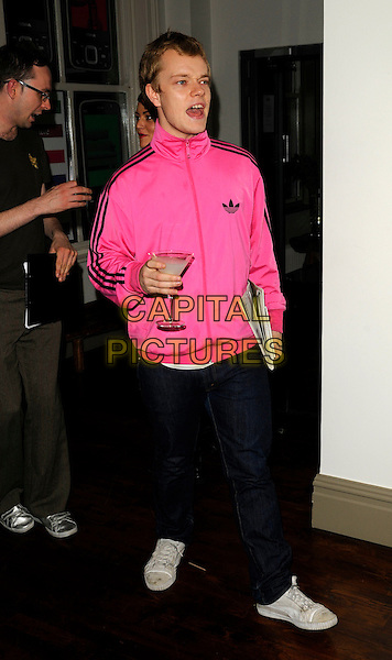 "ALFIE ALLEN  .The Nokia ""Capsule N96"" launch party, Century Club, Shaftesbury Avenue, London, England..September 22nd, 2008.full length jeans denim pink adidas jacket martini glass drink mouth open .CAP/CAN.©Can Nguyen/Capital Pictures."