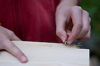 Mädchen baut einen Vogel-Nistkasten aus Brettern, 8. Schritt: Haken anbringen, um Vorderseite später öffnen zu können