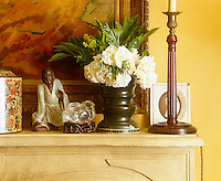An antique canister, carved figurine, crystal bird, candlestick and small posy of roses have all been arranged on the the mantelpiece of the living room fireplace