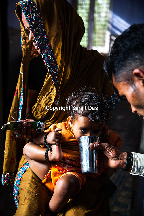 A man feeds water, while his wife feeds a sachet of RUTF to their son at the government health centre in  Hanuman Nagar, Saptari, Nepal.