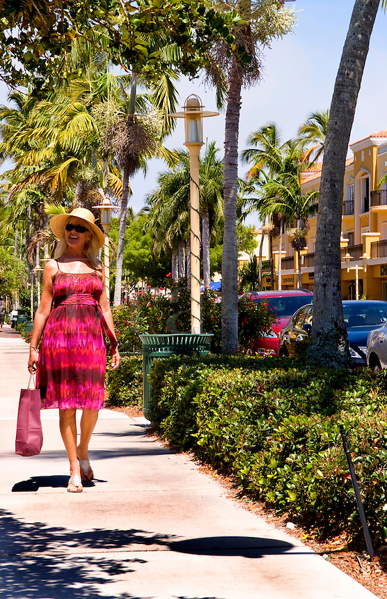 Woman walking and shopping in stylish Naples Florida on trendy 5th Avenue with shopping bag