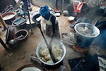 A woman stirs a pot of cooking cassava outside of Abidjan, Cote d'Ivoire.