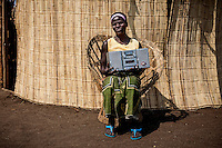 Traditional healer Elvira Chiko (32) sits near her hut with with a radio/cassette tape player.