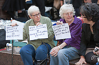 Women hold protest signs in Zuccotti Park during the Occupy Wall Street demonstration in New York City, New York.
