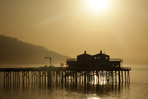 The rising sun provides a silhouette of the Malibu pier along the Pacific Ocean Coast at Malibu, California