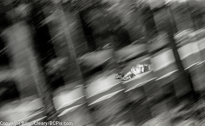 ELKHART LAKE, WI - June 23, 2017: (EDITOR'S NOTE: Photo taken on 35mm black and white film with vintage 35mm rangefinder camera) An IndyCar race car streaks down a straightaway behind slats from a wooden fence during practice for the Kohler Grand Prix Verizon IndyCar race at Road America on June 23, 2017 in Elkhart Lake, Wisconsin. (Photo by Brian Cleary/BCPix.com)