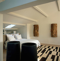 A contemporary, white bedroom with a sloping beamed ceiling. A double bed stands on a patterned, brown and neutral rug. Interesting pieces of recycled material provide texture and warmth to the room.
