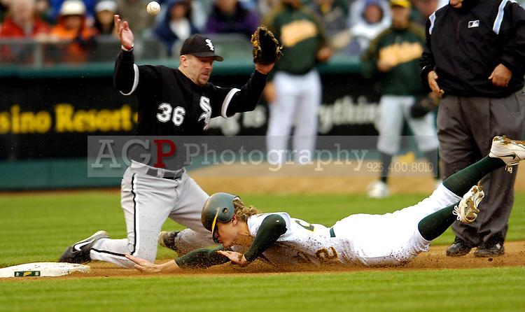 Eric Byrnes of the Oakland A's slides safely into third base as White Sox third baseman Chris Widger can't come up with the throw during eighth inning action  at the Oakland Coliseum Wednesday April 27, 2005. Marco Scutaro's RBI single in the ninth beat the Chicago White Sox 2-1. (Alan Greth/Contra Costa Times)