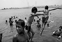 Baghdad, Iraq, June 13, 2003.Children swimming in a pond of sewage soiled irrigation water in Hay Tareq, the poorest slum around Baghdad. The only water available comes directly from the Tigris river through a 30km pipeline; but serious sewer leakage renders it very dangerous....