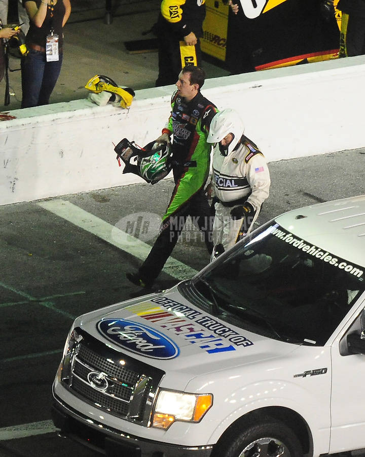 Jul. 4, 2009; Daytona Beach, FL, USA; NASCAR Sprint Cup Series driver Kyle Busch walks with an official after crashing on the last lap of the Coke Zero 400 at Daytona International Speedway. Mandatory Credit: Mark J. Rebilas-